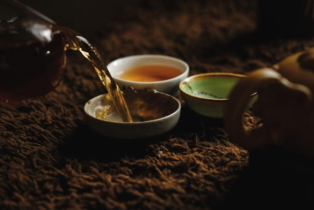 beneficial chinese teas pouring tea bowls dishes cultural around the world health wellness